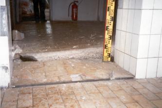 Das Bild zeigt einen gefliesten Fußboden, der im Bereich eines offenen Durchgangs um mehrere Zentimeter abgesackt ist. Deutlich ist die Bruchkante am Boden des angrenzenden Raums zu erkennen.