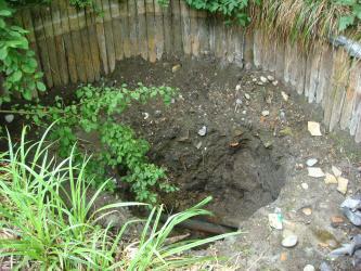 Von einem hölzernen Zaun umgebene Grube im Erdreich; früher wohl mit Wasser gefüllt, jetzt aber ausgetrocknet. Die Grube ist am linken Rand von Grünpflanzen umgeben.