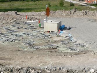 Blick auf eine flache, an den Rändern leicht erhöhte Baugrube mit versenkten Rohren und aufgerollten, aus der Erde kommenden Leitungen.