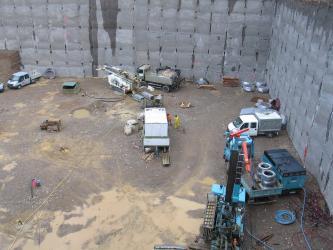 Von erhöhtem Standort blickt man in eine große, ausgeschachtete Baugrube. Verschiedene Fahrzeuge und Materialien stehen oder liegen bereit.