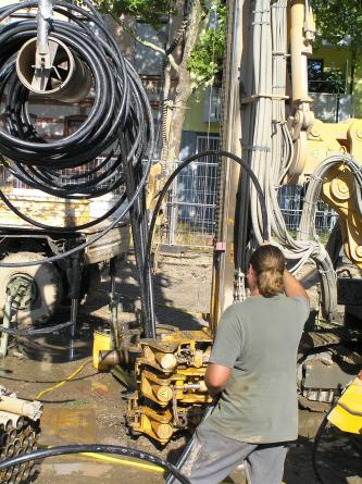 Nahaufnahme eines Bohrgerätes und verschiedener, auf einer Rolle gelagerter Schläuche. Ein Arbeiter lässt einen der Schläuche in ein Bohrloch im Boden hinab.