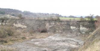 Blick auf eine flache Grube mit unregelmäßig geformtem Gesteinsmaterial in der hinteren Wand. Die Grube ist bewachsen, teilweise ist Erde nachgerutscht. Im Hintergrund Grünland und bewaldete Hänge.