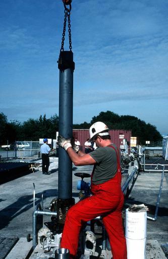 Auf dem Bild setzt ein Mann in Arbeitskleidung ein langes Pumprohr mit Hilfe eines Krans in einen Bohrschacht ein.