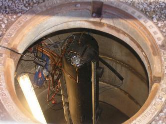 Das Bild zeigt ein in einen Erdschacht hinabgelassenes, zylindrisches Gerät mit angeschlossenen Kupferrohren und Kabeln.