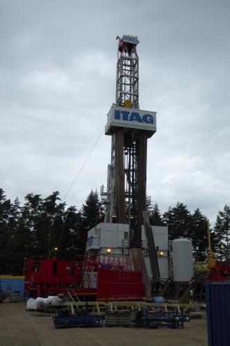 Im Bild ist ein Bohrturm der Firma ITAG, aufgestellt auf planiertem Untergrund. Im Hintergrund ist Wald zu sehen.