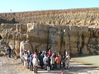 Das Bild zeigt versetzt liegende Abbauwände eines Steinbruches. Die vordere Wand, die rechtwinklig ins Bild ragt, besteht aus großen graubraunen Quadern mit Rissen und Klüften. Eine Besuchergruppe steht davor. Die hintere, hellere Wand ist feiner gebankt.