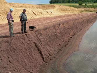 Seitlicher Blick auf unterschiedlich gefärbte, flache Abbauwände einer Grube. Die Wand im Vordergrund ist rötlich gefärbt, die Wände links dahinter sind gelb. Rechts ist Wasser am Boden der Grube zu sehen. Mit auf dem Bild sind zwei Männer und ein Hund.