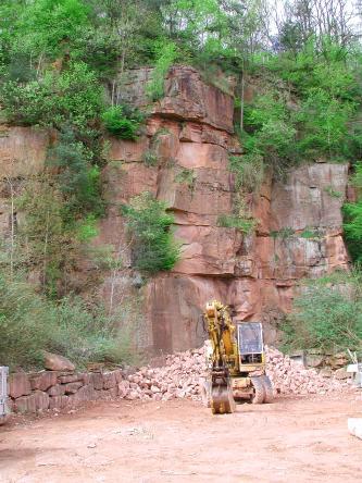 Das Bild zeigt eine stark zugewachsene, rötlich graue Steinbruchwand. Im unteren Bildteil sind Abraumsteine aufgehäuft sowie ein Bagger abgestellt worden.