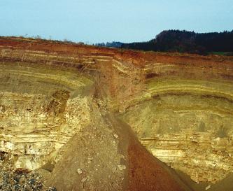 Blick auf mehrere Schichten einer Steinbruchwand, die oben mit rötlichen Tönen beginnen, dann grünlich und schließlich gelblich werden. In der Mitte ist ein Einsturz zu erkennen, rechts bogenförmige Streifen.