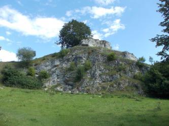 Im Mittelpunkt dieses Bildes steht ein felsiger, teils mit Büschen und Bäumen bewachsener Hügel.