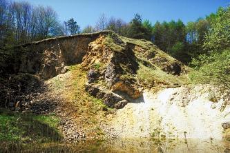Im Vordergrund befindet sich ein See. Dahinter schließt eine steile Wand an, die zum Teil von Gras überwachsen wurde. Hinten befindet sich ein Laubwald.
