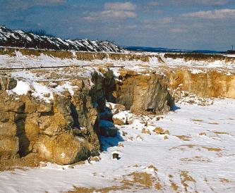 Das Bild zeigt eine rötlich braune, durch Nischen und Klüfte unterbrochene niedrige Gesteinswand, die oben und am Fuß von Schnee bedeckt ist.