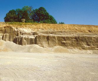 Blick auf den Boden einer Kiesgrube mit kleineren Kieshaufen und nach hinten treppenartig ansteigenden niedrigen Gesteinswänden.
