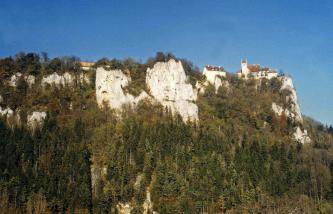 Auf einem hohen bewaldeten Bergrücken ragen teils kleine, teils große weißliche Felsen heraus. Auf einem der Felsen, rechts außen, steht ein Schloss mit Turm und roten Dächern.