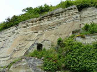 Das Bild zeigt eine hohe, nach rechts ansteigende Felswand mit waagrecht verlaufenden Furchen und Nischen im oberen Drittel. Am Fuß der Felswand ist eine Höhle erkennbar. Rechts unten ist das hellbraune bis graue Gestein bewachsen, ebenso auf der Kuppe.