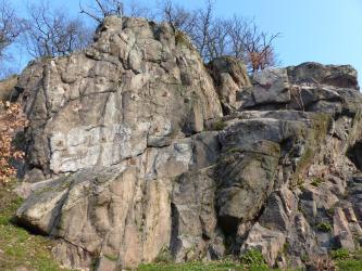 Blick auf ein klippenartige Felsgruppe aus graugrünen Gesteinsblöcken. Die erhöhte Kuppe links ist von Bäumen bewachsen.