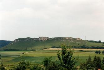 Blick auf einen Bergrücken, der im oberen Teil stellenweise senkrecht ausgebildet ist. Im Vordergrund befinden sich flache Felder und vereinzelt Büsche und Streuobst.