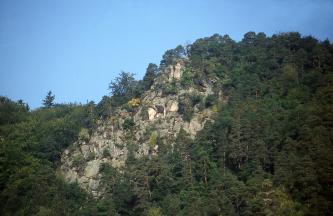 Die Aufnahme zeigt einen nach rechts ansteigenden, dicht bewaldeten Bergrücken mit mittig hervortretenden, grauen Felsen.