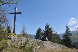 Zu sehen ist hier ein leicht nach rechts abfallendes Felsplateau mit Gipfelkreuz am linken Bildrand. Ein paar Wanderer sitzen auf dem Felsgestein.