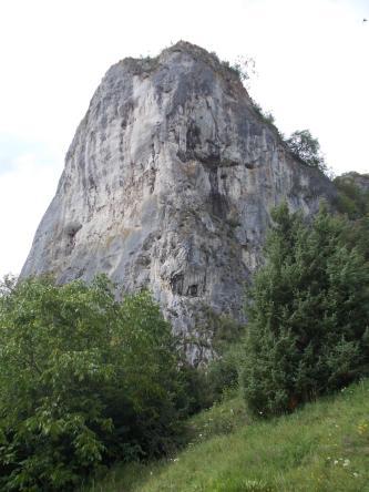 Hinter einem mit Bäumen bestandenen, nach rechts ansteigenden Wiesenhang ragt ein großer grauer Felsenkegel mit Spalten und Nischen auf.