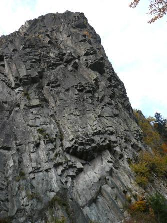 Blick auf einen schwarzgrauen Gesteinsberg mit ziegelartigen, plattigen Formen. Fließrichtung des Berges ist nach rechts.