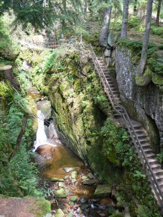 Blick von oben in eine bewaldete Felsschlucht mit Wasserfall links und begleitendem Wanderweg mit Treppen auf der rechten Bildseite.