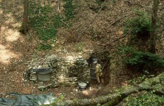 Am Fuße einer steilen, schattigen Böschung  befindet sich ein Höhleneingang. Der Eingang ist seitlich von einer Steinmauer abgestützt und mit einer Tür verschlossen. Ein Mann in Arbeitskleidung öffnet gerade diese Tür oder schließt sie.