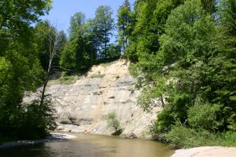 Am Ufer einer Flussbiegung erhebt sich ein steiler, glatter Felshang. Seine Kuppe ist bewaldet. Auch an den angrenzenden und gegenüberliegenden Flussufern stehen Bäume.