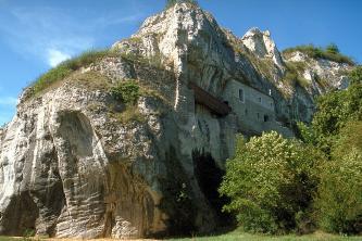 Wie der Bug eines Schiffes ragt ein mächtiger, zum Hintergrund hin abgestufter Felsklotz in dieses Bild. Links vorne weist der Felsen ausgehöhlte Nischen auf. Auf der rechten Seite ist ein hausartiger Vorsprung angebaut, mit Treppen und Holzbrücke.
