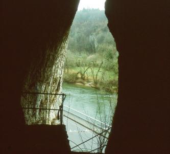 Blick aus einem schmalen, hohen Höhleneingang ins Freie. Die sichtbare Landschaft besteht aus einem Fluß und dessen Uferbereich sowie angrenzendem Wald.