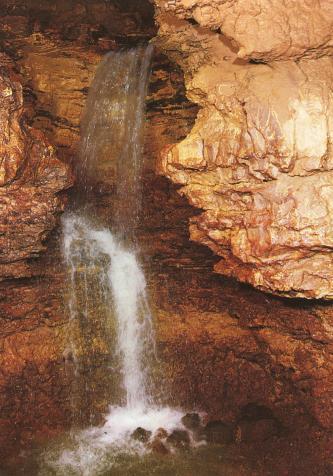 Man sieht das Innere einer Höhle mit stufigem Wasserfall links und diesen eng umschließende, rötlich braune Gesteinswände.
