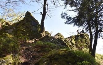 Blick auf mehrere pyramidenförmige Felsblöcke, die an einem Waldhang verteilt sind. Die Felsen liegen teils im Schatten, rechts bieten sie Wanderern Platz. Im Vordergrund liegen flachere, gerundete Felsen. Dazwischen stehen Bäume.