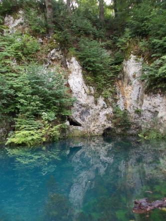 In einer türkisblauen Wasserfläche im Vordergrund spiegeln sich graue, einen Hang bildende Felsen sowie Bäume und Sträucher. Am unteren Ende der Felsen sind kleine Höhlen erkennbar.