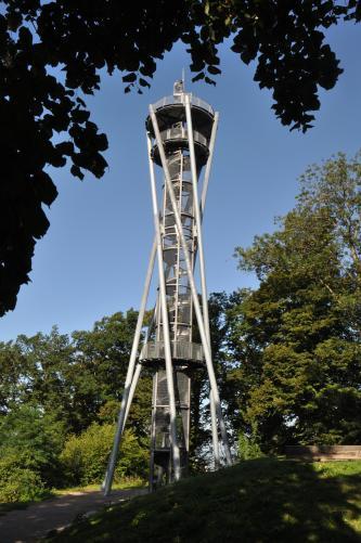 Das Bild zeigt einen Aussichtsturm, der zwischen Bäumen aufragt. Der Turm, der in der Form einer Sanduhr ähnelt, hat Treppen, Geländer und Stützen aus Metall.