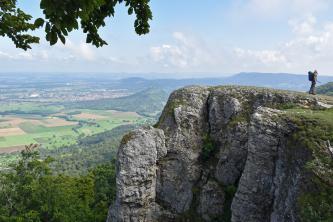 Blick von erhöhtem Standort auf eine rechts vorspringende Felsengruppe, die als Aussichtspunkt dient. Von hier schaut man auf Felder, bewaldete Hügel und Ortschaften herab. Im dunstigen Hintergrund sind noch einige Höhenzüge erkennbar.