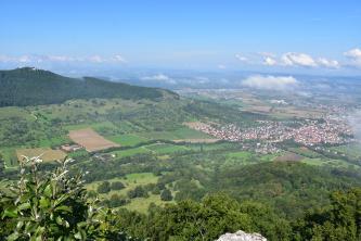 Blick aus großer Höhe über eine weite Landschaft mit Feldern und bewaldeten Hügeln. Rechts verteilen sich mehrere Ortschaften. Nach links hin erhebt sich ein bewaldeter Bergrücken mit einer Burg.