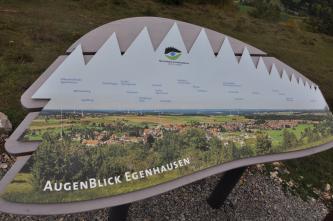 Blick auf eine farbige, auf Holz montierte Fototafel. Die Tafel zeigt eine Landschaft mit Hügeln, Wiesen, Äckern, Wald und Siedlungen. Hinzugefügte Namen von Bergen, Ortschaften oder Sehenswürdigkeiten dienen als Orientierungshilfe.