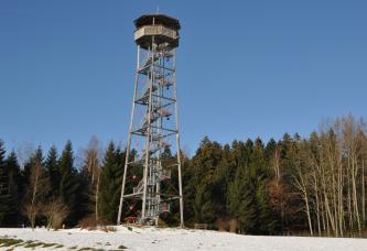 Auf einer mit Schnee bedeckten Anhöhe steht ein Aussichtsturm. Der Turm besteht aus einer offenen Holz/Metallbauweise mit innenliegender Aufstiegstreppe und überdachter Kanzel. Hinter dem Turm stehen Bäume, die der Turm jedoch weit überragt.