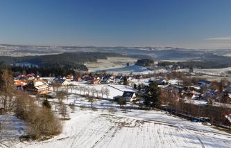 Blick von erhöhtem Standort auf eine verschneite Hügellandschaft mit einer Ortschaft im Zentrum. Dahinter folgen größere Wälder. Am klaren Horizont sind langgestreckte, bewaldete Höhen zu erkennen.