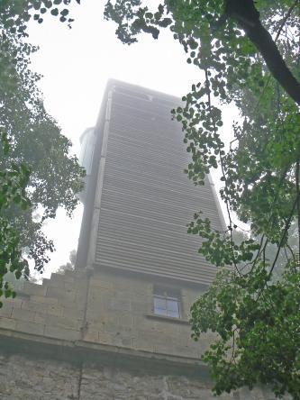 Zwischen belaubten Bäumen ragt ein hoher Turm in einen nebligen Himmel. Der Turm hat eine Basis aus Mauer- und Backsteinen sowie ein Fenster. Der eigentliche Turm besteht aus sowohl senkrecht wie auch waagrecht verbauten Holzbalken.