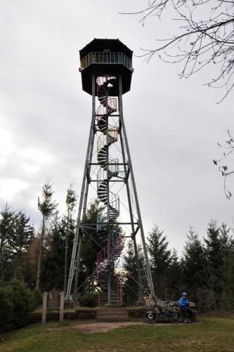 Blick auf einen überdachten, hohen Aussichtsturm aus Metall. Der Turm ist offen und hat eine innen hinaufführende Wendeltreppe, ebenfalls aus Metall. Der Turm steht auf einer Anhöhe, hinter ihm sind Bäume, über die er aber weit hinausragt.