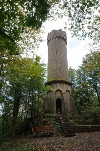 Auf einer Anhöhe im Wald steht ein runder, gemauerter Aussichtsturm, der unten von angesetzten Säulen gestützt wird. Eine Steintreppe führt zum Eingang des Turmes.