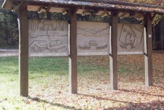 Auf dem Bild sind drei zwischen hölzernen Streben angebrachte Schautafeln mit verschiedenen grafischen Darstellungen, wie zum Beispiel dem Bergbau. Die Tafeln sind überdacht, um sie vor Regen zu schützen.