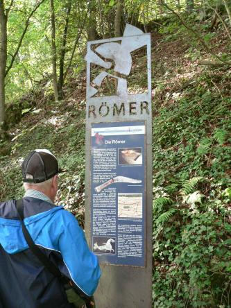 """Am Fuße eines steilen, überwucherten Waldhanges steht eine metallene Informationstafel, die das Thema """"Die Römer"""" hat. Ein Besucher mit Mütze und Jacke sieht sich gerade die Tafel an."""
