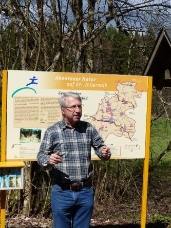 """Vor einer orangefarbigen Schautafel, die das Thema """"Abenteuer Natur auf der Zollernalb"""" hat, steht, möglichen Besuchern zugewandt, ein Mann mit kariertem Hemd."""