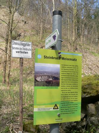 Das Bild zeigt eine an einem mit Bäumen bestandenen Hang aufgestellte Schautafel des Geo-Pfades Eichstetten. Thema der Tafel ist der Steinbruch Meisensatz.