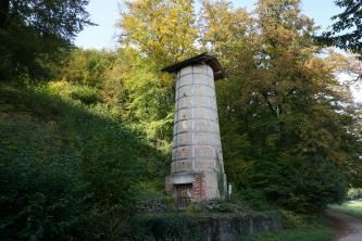 Blick auf einen runden, gemauerten Turm am Fuße eines Waldhanges. Der Turm besteht aus Ziegelsteinen und ist mit Eisenbändern gesichert. Oben ist ein Holzdach aufgesetzt. Unten hat der Turm eine verschlossene Holztür.