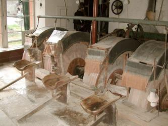 Das Foto zeigt hier eine museale Werkstatt mit vier großen, nebeneinander angeordneten und teilweise abgedeckten Schleifsteinen zum Bearbeiten von Edelsteinen.