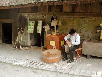 Vor einem alten, als Museum dienenden Bauernhof mit dunklen Steinwänden und noch dunkleren Holzbalken zeigt ein Korbflechter seine Kunst. Links sind zudem Reisigbesen ausgestellt.