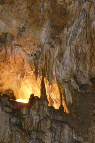 Das Bild zeigt Stalaktiten und Stalagmiten in einer Höhle. Ein Bereich links hinten ist durch künstliches Licht erhellt.